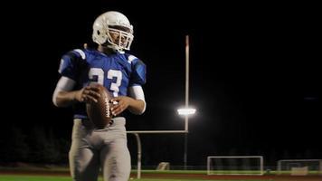 la telecamera gira attorno a un giocatore di football che esegue un'esercitazione sul campo di notte