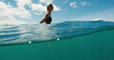 bella ragazza surfista che galleggia sulla tavola da surf nell'oceano blu