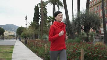 junge Frau, die im Park mit exotischen Sträuchern und Blumen der Palmen läuft