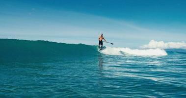 surfista sull'onda blu dell'oceano pende dieci sul naso