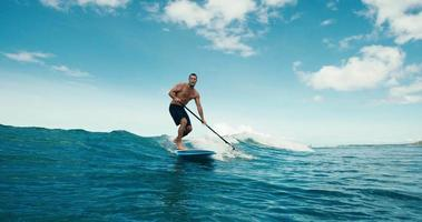 surfista sull'onda blu dell'oceano alzarsi in piedi paddleboarding