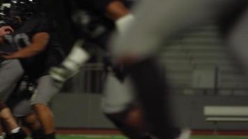 Ein Fußballspieler kämpft sich nachts über das Feld in Richtung Endzone
