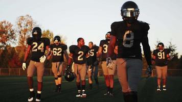 Eine Fußballmannschaft betritt das Spielfeld in goldenem Licht