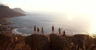 sagome di persone con il sole che tramonta sull'oceano