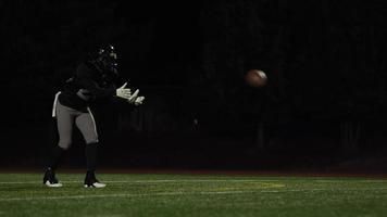 un giocatore di football prende un pallone e lo calcia