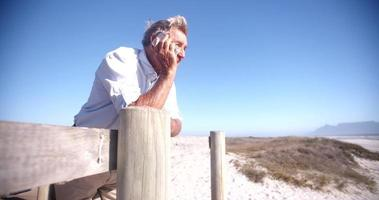Active retired senior on the phone at the beach video