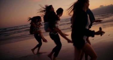 amici hipster facendo divertenti cavalcate sulle spalle sulla spiaggia video