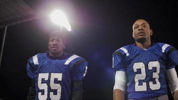 Two football players putting on their helmets and walking onto the field video