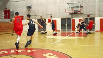 Basketballspieler geben den Ball während eines Spiels über den Platz und machen einen Slam Dunk