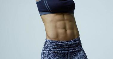 Nahaufnahme des Mittelteils und der Bauchmuskeln der muskulösen jungen Frau, aufgenommen auf r3d