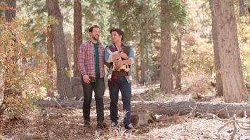 coppia maschio nella foresta con il bambino in imbracatura a piedi verso la telecamera video