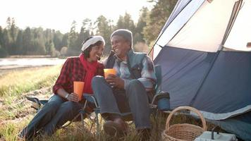 coppia nera senior su un viaggio in campeggio rilassarsi fuori dalla tenda