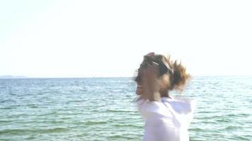 Frau am Strand Musik hören auf Smartphone und tanzen
