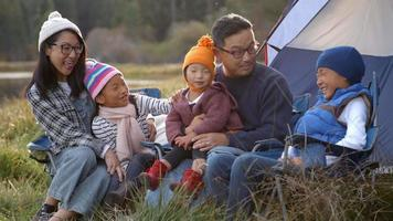 Asian family on a camping trip talking outside their tent