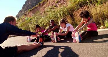 Multiethnische Gruppe von Athleten, die sich während des Trainings auf dem Weg erholen video