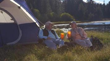 coppia senior seduto fuori dalla tenda vicino al lago, colpo più ravvicinato video