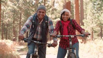 casal negro sênior sentado em uma bicicleta em uma floresta, close-up video