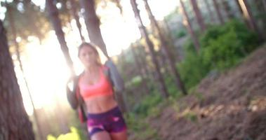 atleta donna sorridente in una foresta con la luce solare mattutina video