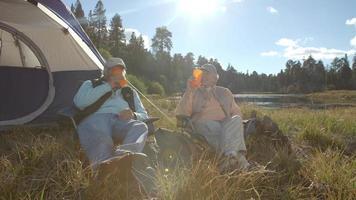 coppia senior seduto fuori da una tenda a bere vicino a un lago