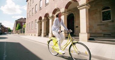 sorridente donna matura in sella alla sua bicicletta attraverso la città vintage