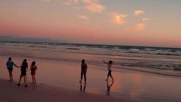 Teen friends enjoying a walk at beach on sunset