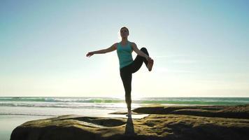 felice giovane donna a praticare yoga sulla spiaggia al tramonto. concetto di stile di vita attivo sano.