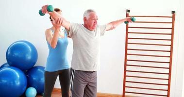 Hombre senior levantando pesas con la ayuda del entrenador video