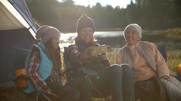madre, figlia e nonna che prendono selfie fuori dalla tenda