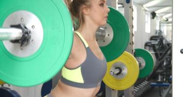 Young woman squat lifting weights at a gym