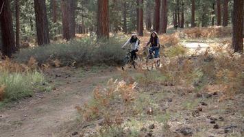 coppia lesbica batti il cinque mentre va in bicicletta in una foresta