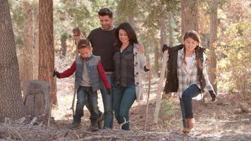 Familia hispana caminando en un bosque, vista frontal de cerca