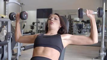 Frau, die mit Hanteln in einem Fitnessstudio trainiert, Nahaufnahme, Schuss auf r3d