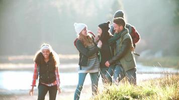 Fünf Freunde auf einem Campingausflug laufen in Zeitlupe in der Nähe eines Sees video