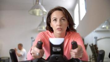 Woman on exercise bike in exercising class at a gym, close up