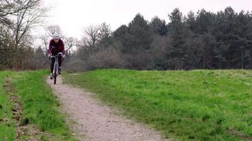 Cross-country cyclist riding down a path in open countryside, shot on R3D