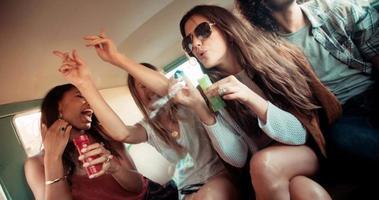amici hipster che fanno festa con le bolle all'interno di un furgone vintage video