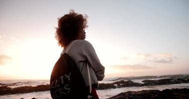 chica afro hipster lanzando una piedra al océano