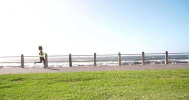 Afro-Amerikaanse atleet joggen om fit te blijven langs het strand