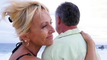 Nahaufnahme eines älteren Paares am Strand mit ihren Armen umeinander, wobei die Frau in die Kamera lächelt