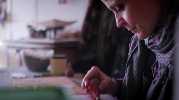 Creatore di ceramica riempiendo tratti di matita su terracotta con primo piano di padella tenuto in mano con bulbo di gomma
