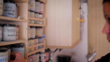 fabricante de cerâmica selecionando cores e esmaltes em potes de plástico video