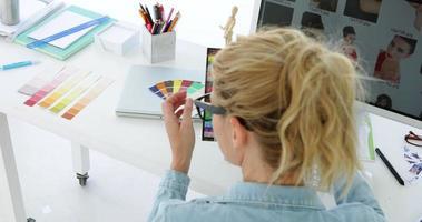 retrovisor da designer loira trabalhando em sua mesa
