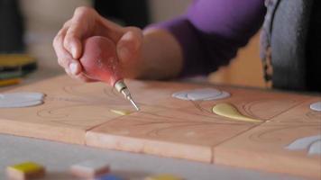 ceramista che riempie tratti di matita su terracotta con bulbo di gomma davanti a campioni di colore