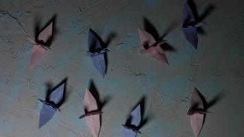 4k disparar de grullas de origami sobre un fondo con luz en movimiento