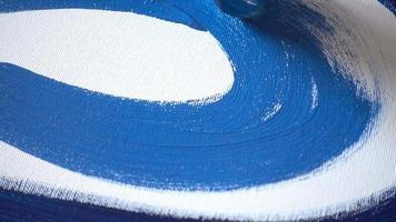 artista pintando un cuadro azul con lienzo blanco