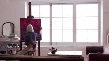 artista trabalha pintando em estúdio à luz do dia em r3d video