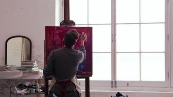 artista masculino trabalha pintando em estúdio à luz do dia em r3d video