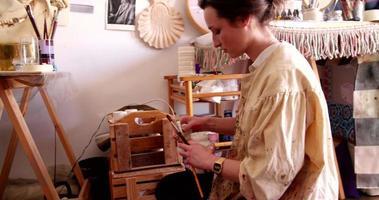 un'artista che controlla la sua pittura con i suoi pennelli