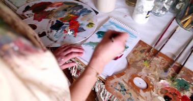 Artista pintando sobre papel sobre una mesa de estudio desordenada