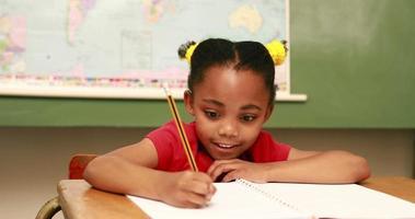 pupilla felice scrivendo nel blocco note alla scrivania